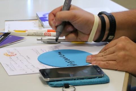 """ein Tisch mit Smartphone und Schreibunterlagen; jemand schreibt das Wort """"Ressourcen"""" auf ein Stück Papier"""